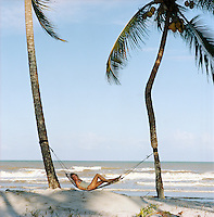 Portrait of Charlene de Ganay reclining in a hammock hung between two palm trees on the beach