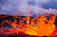Yellow and orange molten lava splashes upwards against a background of grey clouds.