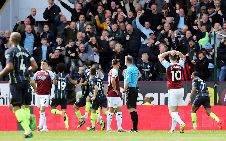 Burnley's Ashley Barnes is left dejected as Manchester City's Sergio Aguero celebrates with team-mates after Matthew Lowton failed to prevent his strike crossing the line for the opening goal<br /> <br /> Photographer Rich Linley/CameraSport<br /> <br /> The Premier League - Burnley v Manchester City - Sunday 28th April 2019 - Turf Moor - Burnley<br /> <br /> World Copyright © 2019 CameraSport. All rights reserved. 43 Linden Ave. Countesthorpe. Leicester. England. LE8 5PG - Tel: +44 (0) 116 277 4147 - admin@camerasport.com - www.camerasport.com