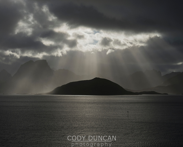 Dramatic autumn light shines over fjord and distant mountain peaks, Moskenesøy, Lofoten Islands, Norway