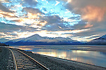 Train tracks and mountains are illuminated by the sunrise over Turnagain Arm in south central Alaska.