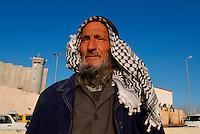ABU DIS / GERUSALEMME / ISRAELE.DERAJ MUSA ALI AZATE, 76 ANNI NEI PRESSI DELLE ROVINE DELLA SUA CASA. SULLO SFONDO IL MURO ED IL CHECKPOINT DELL'ESERCITO ISRAELIANO CHE CONTROLLA I PALESTINESI IN ENTRATA A GERUSALEMME..NEL 2004 L'ESERCITO ISRAELIANO GLI HA DISTRUTTO LA CASA E CONFISCATO LA TERRA CHE SI TROVAVA NELL'AREA IN CUI E' STATO COSTRUITO IL MURO. .DA ALLORA VIVE CON LA SUA FAMIGLIA A CASA DEL FRATELLO..FOTO LIVIO SENIGALLIESI..ABU DIS / JERUSALEM / ISRAEL.IN THE PICTURE MR.DERAJ MUSA ALI AZATE (76) NEAR THE RUINS OF HIS HOUSE. THE ISRAEL DEFENCE ARMY DESTROYED HIS HOUSE AND CONFISTATED HIS LAND IN 2004 WHEN THE ISRAELI GOVERNAMENT DECIDED TO BUILD THE SECURITY FENCE..PHOTO LIVIO SENIGALLIESI