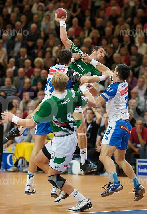 Handball 1.Bundesliga Herren 2009/2010, EWS Arena Goeppingen (Germany), FrischAuf Goeppingen - HSV Hamburg (36:35), Michael Haass (FAG) im Sprungwurf, rechts Matthias Flohr (HSV), links Krzysztof Lijewski (HSV), vorne Manuel Spaeth (FAG)