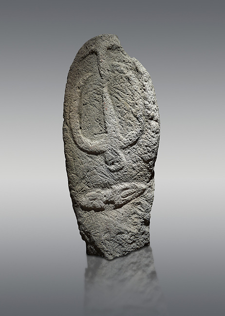 Late European Neolithic prehistoric Menhir standing stone with carvings on its face side. The representation of a stylalised male figure starts at the top with a long nose from which 2 eyebrows arch around the top of the stone. below this is a carving of a falling figure with head at the bottom and 2 curved arms encircling a body above. at the bottom is a carving of a dagger running horizontally across the menhir.  Excavated from Barrili II site,  Laconi. Menhir Museum, Museo della Statuaria Prehistorica in Sardegna, Museum of Prehoistoric Sardinian Statues, Palazzo Aymerich, Laconi, Sardinia, Italy. Grey background.
