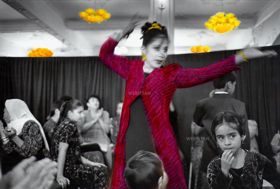 2002. Afghanistan. Kabul. A woman dances in the middle of other women in the side of the party hall, reserved to women. There is a curtain separating men from women so that women can dance freely away from the men's gaze. Afghanistan. Kaboul. Une femme danse parmi d'autres dans la partie de la salle des fêtes réservée aux femmes. Il y a un rideau qui sépare les femmes des hommes, pour que les femmes puissent danser loin des regards.