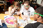 Education High School science lab male and female students wearing goggles doing lab, girl  taking an active role