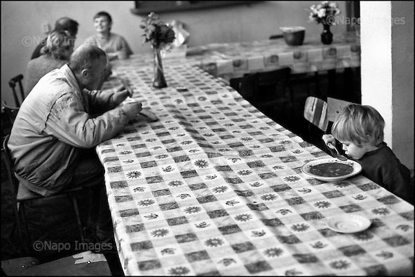 Hrubieszow,  South East Poland November 2005<br /> The faces of Polish poverty<br /> Dinner at the shelter for the poor and homeless in Hrubieszow<br /> ( &Scaron; Filip Cwik / Napo Images for Newsweek Polska)<br /> <br /> Hrubieszow k.Zamoscia 26 listopad 2005 Polska<br /> Oblicza biedy w Polsce<br /> Stowarzyszenie Przeciwdzialania Patologiom Spolecznym KRES prowadzi Ryszard Karpinski ktory wraz z czworka dzieci i zona mieszka w osrodku. Przebywa w nim 30 osob doroslych i 13 dzieci. Osrodek pobiera oplate w wysokosci 35 % przychodow mieszkanca /z emerytury , renty , zapomogi itp. /. Oferuje w zamian trzy cieple posilki dziennie, pokoj i ciepla wode.<br /> Wiekszosc Polakow niemal / 85% / z trudem radzi sobie z przezyciem od pierwszego do pierwszego. Ponad polowa / 52,5% / zalega ponad trzy miesiace z czynszem. Tyle samo osob, aby poprawic swoja sytuacje materialna radykalnie ogranicza wydatki. W beznadziejnej sytuacji jest ludnosc wiejska gdzie 18,5% zyje w skrajnej nedzy. W 1991 roku rzad polski zlikwidowal Panstwowe Gospodarstwa Rolne ktore od II Wojny Swiatowej byly miejscem pracy dla ponad 2 mln rolnikow glownie na ziemiach odzyskanych. Ci ludzie i ich rodziny nie odnalezli sie w nowej rzeczywistosci<br /> ( &Scaron; Filip Cwik / Napo Images dla Newsweek Polska)