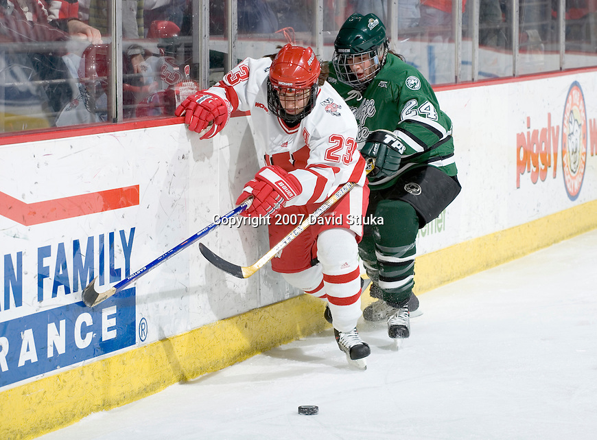 MADISON, WI - FEBRUARY 16: Phoebe Monteleone #23 of the Wisconsin Badgers women's hockey team battles for the puck against Ashley Leopold #24 of the Bemidji State Beavers at the Kohl Center on February 16, 2007 in Madison, Wisconsin. The Badgers beat the Beavers 2-0. (Photo by David Stluka)