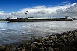 ZALTBOMMEL - Een binnenvaartschip met vracht en een Nederlandse vlag achterop vaart over de rivier de Waal.  COPYRIGHT TON BORSBOOM