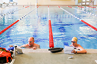 John Amsden of Bella Vista (from left) and Hailey Venter of Bentonville read over their swimming routine before swimming laps, Monday, May 18, 2020 at the Bentonville Community Center in Bentonville. Community Center staff opened the pool for members 16 and older and for lap swimming only Monday. Members interested in swimming were required to register for an appointment in advance. Check out nwaonline.com/200519Daily/ for today's photo gallery.<br />