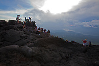 Hikers gather on cooled lava on Volcan Pacaya in Guatemala. A stream of hot lava is nearby.