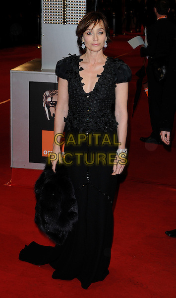 KRISTIN SCOTT THOMAS.in Louis Vuitton.Arrivals at the Orange British Academy Film Awards 2010 at the Royal Opera House, Covent Garden, London, England, UK, .21st February 2010.BAFTA BAFTAs full length black long maxi dress buttons fur silver cuff bracelet diamond .CAP/CAN.©Can Nguyen/Capital Pictures
