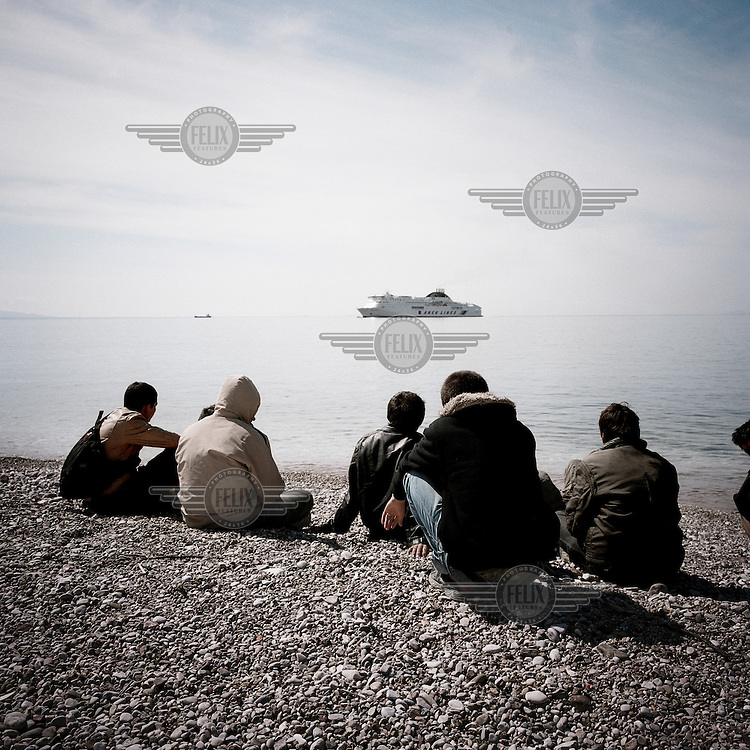A group of refugees sit on a beach as they watch an approaching ship. Patras is home to about 3,000 illegal immigrants. Most of them are Afghans, although there are also some Iranians and Uzbeks. They stop in Patras to try and find passage to various European destinations by hiding in ships, containers and trucks parked in the port. If they are lucky they will make it to their destination. Many of them live in shacks made from cartons, plastic and wood they found on the beach. To shelter from the cold they also squat in abandoned buildings, living without water and electricity. The living conditions are inhumane and unhygienic.