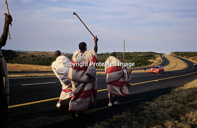 Unidentified Xhosa boys greets people driving in a National highway as they are going trough a traditional manhood ceremony on July 19, 2001 in Mdantsane, South Africa. The ceremony lasts for about six weeks starting with a circumcision. The wound has to be healed in a natural way, and elders guide the boys during the ceremony, which is to prepare them for adulthood. Former South African president Nelson Mandela went trough the ceremony when he was young. (Photo by: Per-Anders Pettersson)