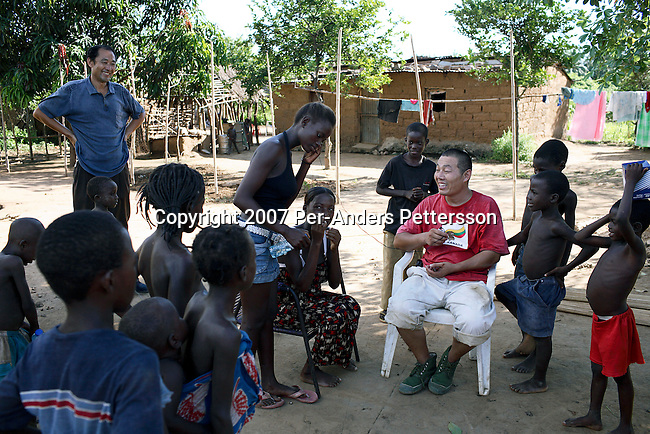 DONDO, ANGOLA APRIL 1: Chinese railway workers interact with villagers while taking a break from work on April 1, 2007 in Dondo, about 200 kilometers outside Luanda, Angola. Chinese companies are building and upgrading two different railways in Angola, and this part is about 500 kilometers long. All the special equipment has been shipped from China and hundreds of workers live in military style road camps. They are moved as the tracks are laid down. Tens of thousands of Chinese has come to Africa the last years to work in infrastructure projects and businesses. Chinese companies are often the lowest bidders for contracts, pricing out the more expensive European companies. The Chinese people often live where they work and rarely interact with the local population. Most Chinese don't speak English and they are mostly staying in the compounds cooking their Chinese food. (Photo by Per-Anders Pettersson)...