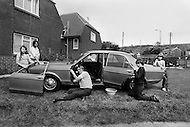 August 1981. Newcastle area, England. Mr. Laverton from Grove, unemployed from Royal Mail for 8 months, repairs his neighbors cars with his 4 kids to earn a little income.