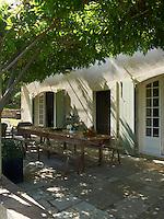 A wisteria covered pergola shades the al fresco dining area