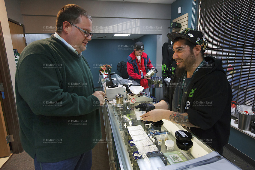 USA. Colorado state. Denver. Customers buying cannabis and employees selling it in the medical marijuana section at Medicine Man. Jesse Toks (R) advices a buyer on various cannabis products used for dabbing which is a slang term used to describe taking single dose hash hits of concentrates that are referred to as oil, erl, earwax, wax, budder, BHO or shatter. Medicine Man began nearly six years ago as a small medical marijuana operation and has since grown to be the largest single marijuana dispensary, both recreational and medical, in the state of Colorado and has aspirations of becoming a national brand if pot legalization continues its march. Cannabis, commonly known as marijuana, is a preparation of the Cannabis plant intended for use as a psychoactive drug and as medicine. Pharmacologically, the principal psychoactive constituent of cannabis is tetrahydrocannabinol (THC); it is one of 483 known compounds in the plant, including at least 84 other cannabinoids, such as cannabidiol (CBD), cannabinol (CBN), tetrahydrocannabivarin (THCV), and cannabigerol (CBG). 18.12.2014 © 2014 Didier Ruef
