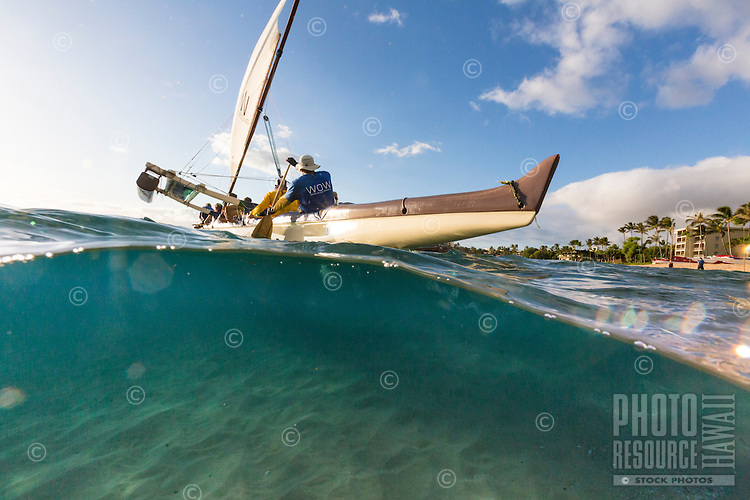 An over-and-under image of Ka'anapali Beach with a Hawaiian sailing canoe, Maui.