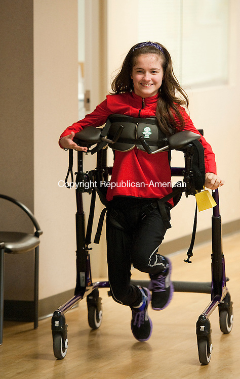 MIDDLEBURY, CT 07MARCH  2013-030713JS01-- Meg Moore, 16, a sophomore at Pomperaug High School, run through the halls of the Alliance Medical Group in Middlebury on Thursday. Moore, despite having cerebral palsy and needing the use of a walker, is on the track team at Pomperaug High School. .Jim Shannon Republican-American.