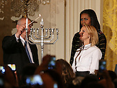 The grand-daughter and son of Shimon Peres, Mika Almog (R) and Chemi Peres (L) lit the menorah while United States President Barack Obama (unseen) and First Lady Michelle Obama (C) watch during the second Hanukkah reception of the day in the East Room of the White House, December 14, 2016, Washington, DC. <br /> Credit: Aude Guerrucci / Pool via CNP