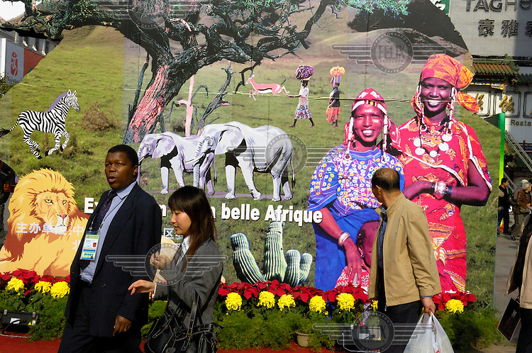 An African delegate passes a propaganda poster for the 2006 China-Africa Summit, which celebrated fifty years of diplomatic relations and was intended to strengthen the political and economic ties between China and Africa.