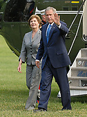Washington, D.C. - June 11, 2007 -- United States President George W. Bush, right, waves to photographers as he and first lady Laura Bush, left, return to the White House aboard Marine 1 after an eight day visit to Europe in Washington, D.C. on Monday, June 11, 2007.  <br /> Credit: Ron Sachs - Pool