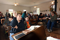 NWA Democrat-Gazette/FLIP PUTTHOFF<br />ONE ROOM SCHOOL<br />Walker Logan (foreground left), 13, and his desk mate Thomas Horn, 11, take part in lessons Wednesday Oct. 11 2017 at the one-room Rocky Branch School east of Rogers near Beaver Lake. Area students from Connections Academy, a tuition-free online public school, held class at the historic school Wednesday and pretended they were in school during 1905. Cathy Orr with the Rogers Historical Museum taught the students.