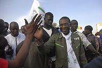 xnb02 DAKAR (SENEGAL) 28/1/2012.- Foto disponible desde hoy, sábado 28 de enero de 2012 que muestra al músico senegalés Youssou N'Dour (d), durante una acto de campaña en Dakar, Senegal, el 27 de enero de 2012. Los enfrentamientos entre manifestantes y fuerzas de seguridad causaron un muerto en Dakar, según informaron hoy varias emisoras de radio privadas, que cita fuentes policiales. La víctima, perteneciente a las fuerzas de seguridad, resultó herido grave en los choques y murió poco después de su traslado a un hospital de la capital de Senegal. La violencia se ha extendido a varias localidades del interior del país, donde miles de jóvenes protagonizaron disturbios en protestas por la decisión del Consejo Constitucional de habilitar la candidatura del actual mandatario, Abdoulaye Wade, para las elecciones presidenciales del próximo 26 de febrero. .EFE/ALIOU MBAYE