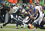 Seattle Seahawks defenders, Steven Terrell (23), K.J. Wright (50) and Bobby Wagner (54) team up to bring down Denver Broncos running back C.J. Anderson during the first quarter at CenturyLink Field on August 14, 2015 in Seattle Washington.  The Broncos beat the Seahawks 22-20.  © 2015. Jim Bryant Photo. All Rights Reserved.