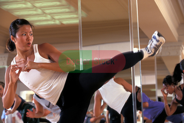 young woman instructor showing kickboxing move in health club studio