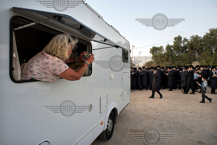A traveller takes a photo, out of her caravan window, of Ultra-Orthodox Jewish men and boys praying during a 'Tashlich' ritual beside the Mediterranean Sea. 'Tashlich' ('to cast away') is a ritual where believers go to a flowing body of water and symbolically 'throw away' their sins. It takes place before the Day of Atonement ('Yom Kippur'), the holiest day in the Jewish calendar.