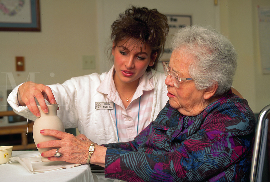 A smiling senior woman works on a craft assisted by a caregiver at a nursing home.