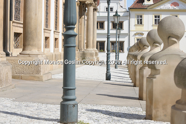 A street with green lamps, posts, and buildings near Prague Castle in Prague, Czech Republic.