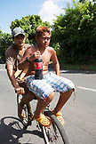 FRENCH POLYNESIA, Tahiti. A couple of boys on a bicycle with bread and bottle of coke in the village of Vairao located along the southern coastline of Tahiti Island.