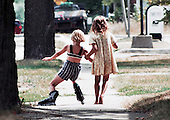 In stride: A young girl learns how to roller blade with help from a friend during a hot day in August.