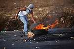 A Palestinian protester burn tires during clashes with Israeli troops near the Jewish settlement of Bet El, near the occupied West Bank city of Ramallah October 5, 2015. Violence intensified in Jerusalem and the West Bank on Sunday after Israelis were targeted in two stabbing attacks and a Palestinian was killed in a clash with Israeli troops, officials said. Photo by Shadi Hatem