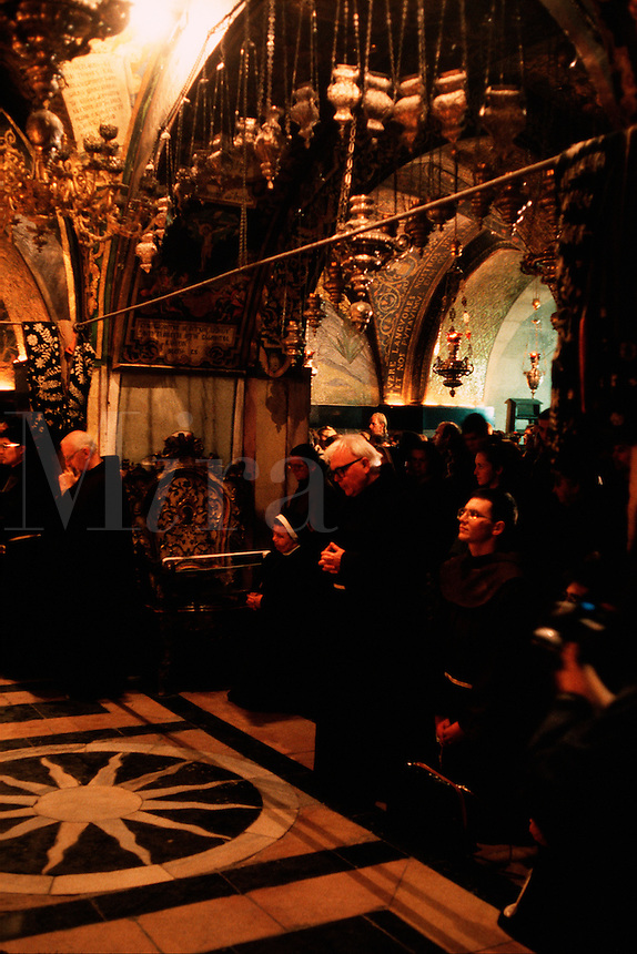 Monks and pilgims kneel in prayer in the Armenian Orthodox Church of the Sepulchre. Jerusalem, Israel.