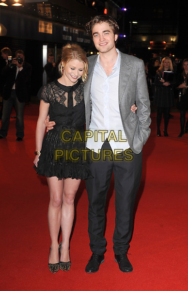 """EMILIE DE RAVIN & ROBERT PATTINSON .UK Premiere of """"Remember Me"""" - Arrivals, Odeon Leicester Square, London, England, UK, 17th March 2010..full length black dress lace sheer see thru through bow bare legs shoes gold studded studs bracelet ruffles ruffle tiered arm around grey gray jacket blazer blue shirt hand in pocket trousers .CAP/BEL.©Tom Belcher/Capital Pictures ."""