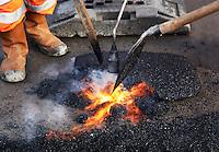 Wegwerkerkers zijn een weg aan het asfalteren
