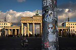 Sun reflecting on the columns of the Brandenburg Gate in central Berlin, which acted as a section of the Berlin Wall. The route of the Wall, which stood from 1961-1989, has been developed into the 'Mauerweg,' a thoroughfare which traces most of the route of the Wall which encircled the city and divided it into East and West Berlin during the Cold War. In the years following the 1989 civil uprising in the German Democratic.Republic, most of the Wall was removed as part of the reunification strategy which united the pro-Soviet DDR and the Federal Republic of (West) Germany.