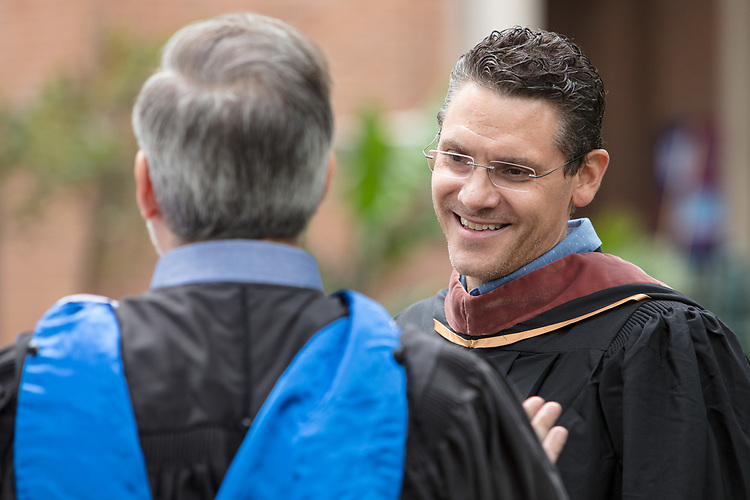 Brad Riddell, assistant professor in the School of Cinematic Arts, converses with colleagues before processing to the 120th DePaul University Convocation on Thursday, August 31, 2017, at St. Vincent de Paul Parish Church. DePaul University President A. Gabriel Esteban, Ph.D., and Marten denBoer, provost, provided remarks, and many faculty and staff were recognized with annual awards including: Excellence in Teaching, Spirit of Inquiry, Excellence in Public Service, Vincent de Paul Professorship, Spirit of DePaul, Staff Quality Service, Gerald Paetsch Academic Advising and faculty promotion and tenure. (DePaul University/Jeff Carrion)