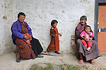 Women and children in traditional dress. A traditional Puja celebration, a yearly Buddhist festival by the local community, Chuchizshey temple, Bumthang, Bhutan..Bhutan the country that prides itself on the development of 'Gross National Happiness' rather than GNP. This attitude pervades education, government, proclamations by royalty and politicians alike, and in the daily life of Bhutanese people. Strong adherence and respect for a royal family and Buddhism, mean the people generally follow what they are told and taught. There are of course contradictions between the modern and tradional world more often seen in urban rather than rural contexts. Phallic images of huge penises adorn the traditional homes, surrounded by animal spirits; Gross National Penis. Slow development, and fending off the modern world, television only introduced ten years ago, the lack of intrusive tourism, as tourists need to pay a daily minimum entry of $250, ecotourism for the rich, leaves a relatively unworldly populace, but with very high literacy, good health service and payments to peasants to not kill wild animals, or misuse forest, enables sustainable development and protects the country's natural heritage. Whilst various hydro-electric schemes, cash crops including apples, pull in import revenue, and Bhutan is helped with aid from the international community. Its population is only a meagre 700,000. Indian and Nepalese workers carry out the menial road and construction work.