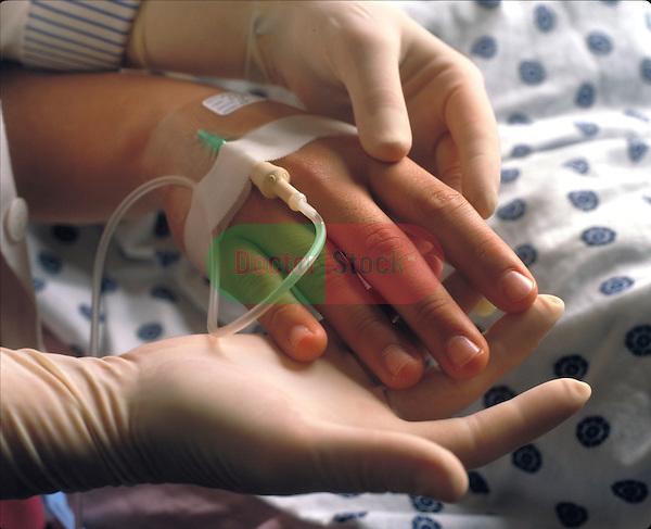 technician examining IV in patient's hand