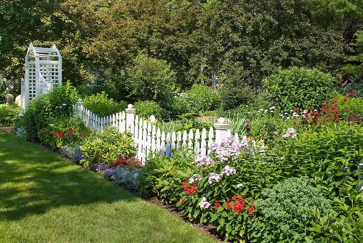 Picket fence garden of perennials and annuals plant flower stock white picket fence undulating with flower garden arbor lawn grass fragrant phlox mightylinksfo