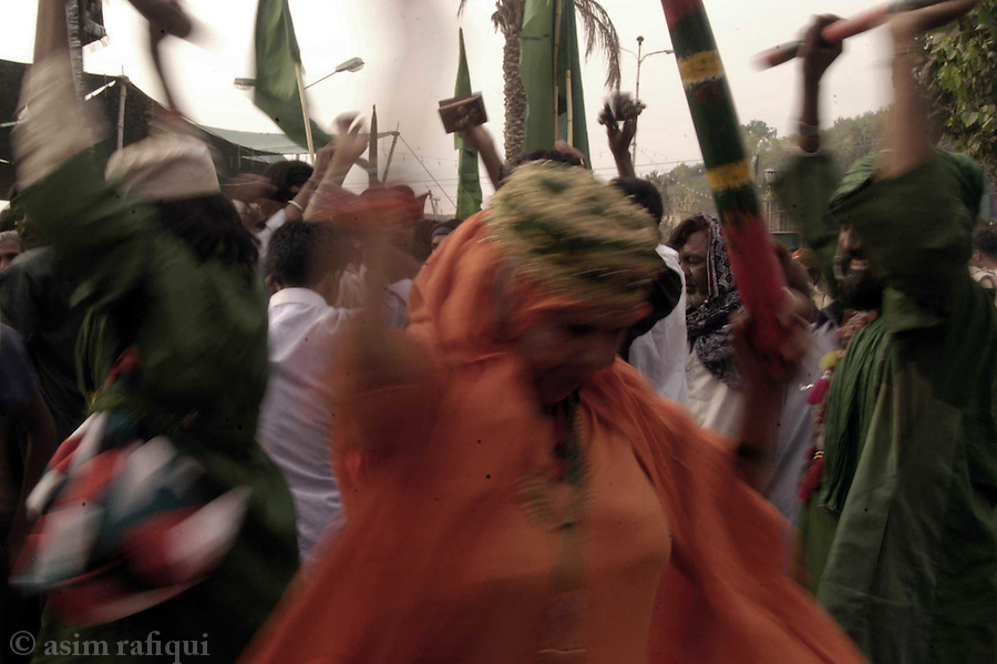bari imam shrine, islamabad, pakistan 2004: in a swirl of color, devotess dance as they make their way to the bari imam shrine.<br />