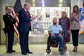 US President Donald J. Trump (2-L), with First Lady Melania Trump (R), applaud Sergeant First Class Alvaro Barrientos (C), with his wife Tammy Barrientos (2-R), after awarding him the Purple Heart during a visit to Walter Reed National Military Medical Center in Bethesda, Maryland, USA, 22 April 2017. Sergeant First Class Alvaro Barrientos was recently injured in Afghanistan while deployed and for the wounds he sustained, he is receiving the Purple Heart.<br /> Credit: Shawn Thew / Pool via CNP