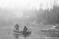 Two men paddle their motor boat on a misty lake on a moose hunt.