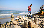 A Palestinian youth Ahmed Al Awadi performs rock balancing at the beach of Gaza city on November 16, 2017. Rock balancing is a performance art which involves arranging natural stones usually found on location, in gravity-defying alignments without the need of any additional tools. Photo by Hassan Jedi