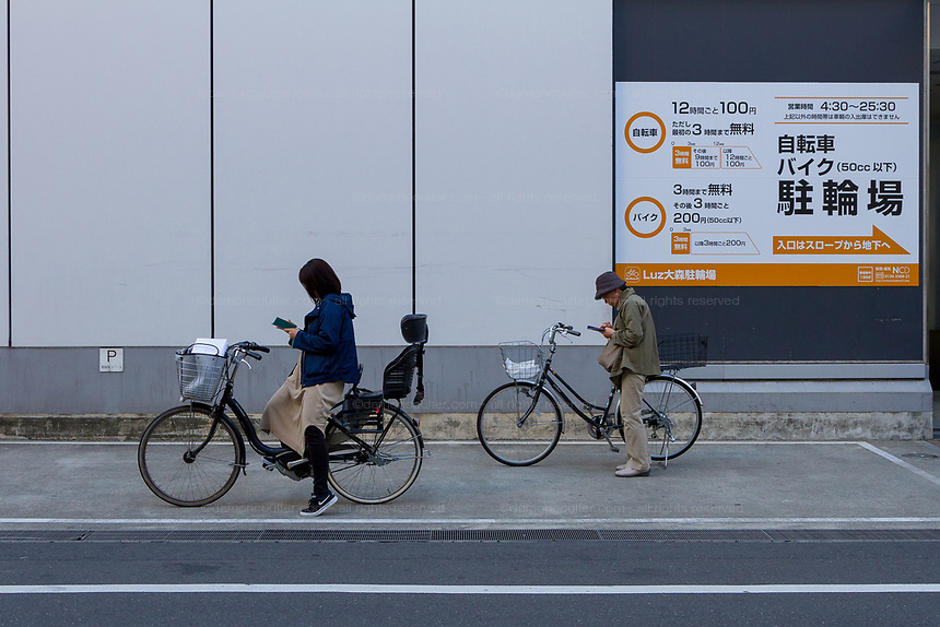 An older woamn stands by her bicycle to use a smartphone while a  younger woman rests on her biccyle while using her own smartphone also, in a street Omori, Tokyo, Japan. Friday November 15th 2019